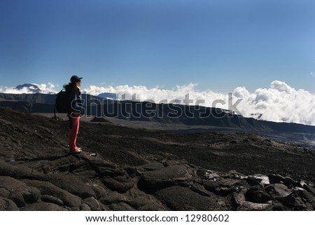 A trekker on top of a volcano, above clouds (Reunion Island/Africa).