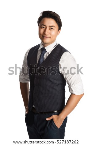 A trendy and fashionable businessman wearing a blue vest, tie and shirt. Standing against a white background smiling.