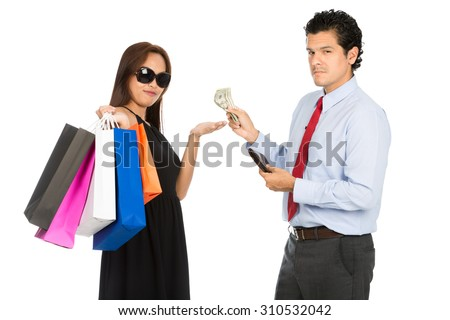 A trendy Asian woman shopaholic with black dress, sunglasses and department store bags accepts money from her wealthy husband looking at camera. H - stock photo