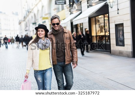 A trendy couple is walking in the city center. They are in a cobbled car-free street. The woman is wearing a black hat and a pink shopping bag and the man has sunglasses and a leather coat - stock photo