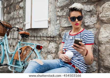 A trendy young female watching her photo on cell telephone while relaxing near her bicycle during free time. - stock photo