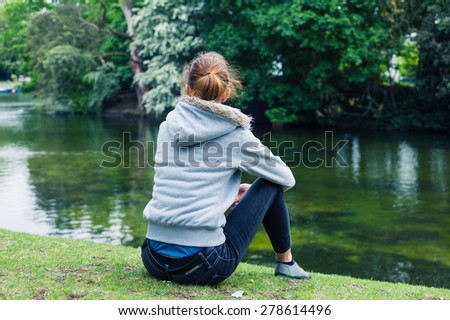 A trendy young woman is sitting by the water in a park