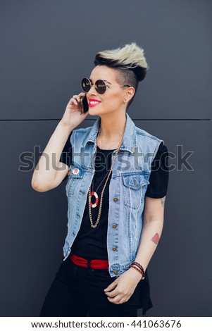 A trendy young woman talking on her cell phone while standing against a grey background - stock photo