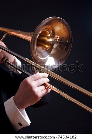 A trombone is held by the hands of a man in a tuxedo, isolated on black. - stock photo