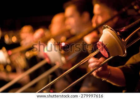 A trombone section playing together in a traditional big band jazz ensemble. Selective focus on the foreground trombone.   - stock photo