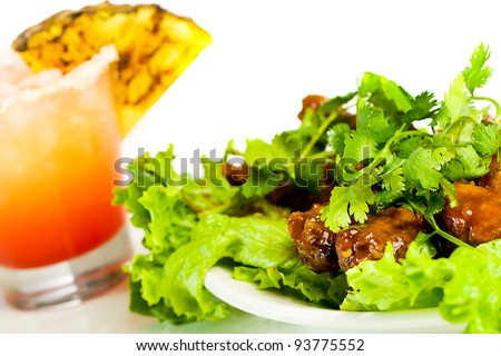 A tropical, fruity drink with a plate of barbecue buffalo chicken wings. - stock photo