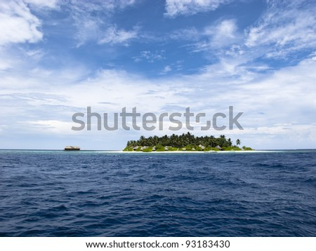 A tropical island in blue lagoon and ocean with cloudy sky - stock photo