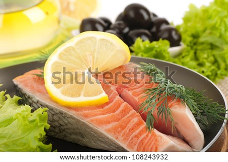 A trout is fried with a pepper and basil, tomatoes and field flowers - stock photo