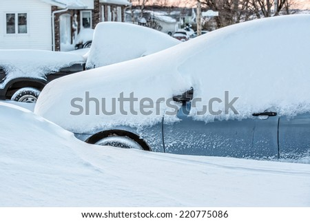 A truck and a car in a driveway in a suburban neighborhood buried in new fallen snow. - stock photo