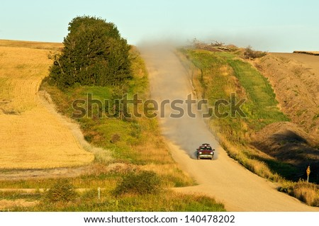 A truck descending a rural road in the early morning - stock photo