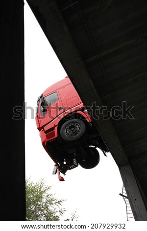 A truck hangs off a parking deck after a break through of the railings - stock photo