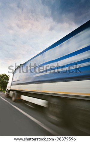 A truck in high speed as seen from lateral side. Useful file for your corporate brochure, annual reports and other media about transportation, logistics etc. - stock photo