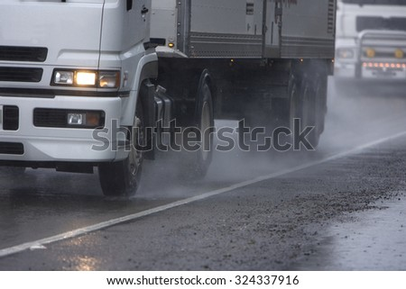 A truck moves along a rainy road, spray coming out from the side around the tires. Lots of copy space. - stock photo