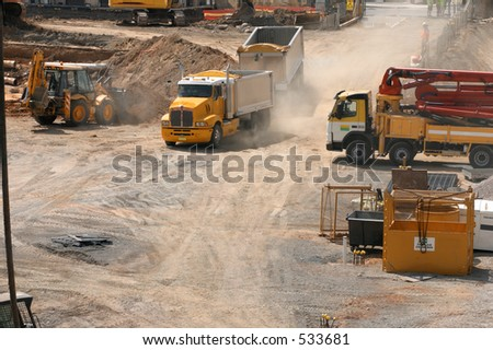 A truck rumbles into a construction site.  An earthmover scoops up a load of dirt and there are workmen in discussion. - stock photo