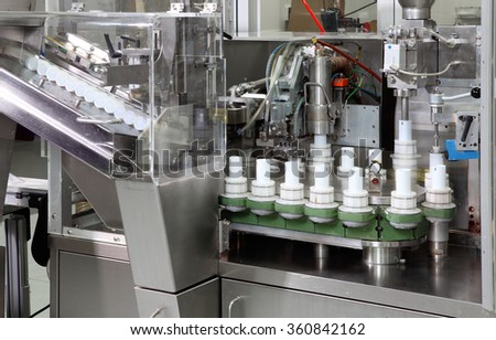 A tube filling machine in a cosmetics factory. - stock photo