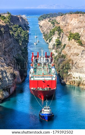 A tug boat pulling a freight ship though the Corinth Canal, Greece. - stock photo