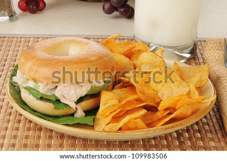 A tunafish sandwich on a bagel with potato chips