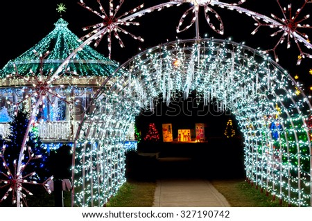 A tunnel of lights and icicle decorations with a festively lit gazebo at Christmas - stock photo
