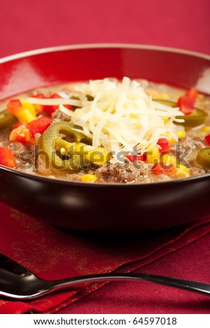 """A turkey based """"white chili"""" topped with cheese and peppers - stock photo"""