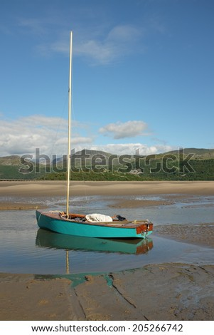 A turquoise sail dinghy floats in a puddle on tha sand of an estuary with mountains in the distance.