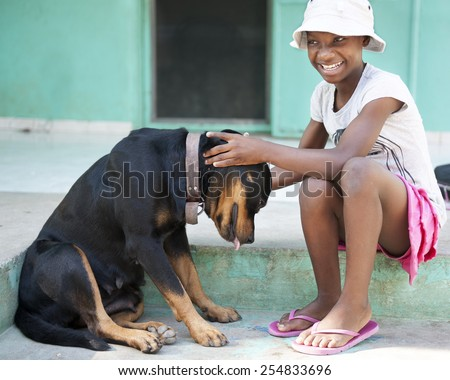 A tween Haitian girl happily petting a large black dog.   - stock photo