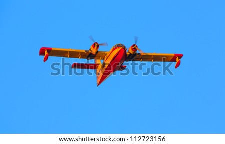 A twin-engined water bomber over blue sky - stock photo