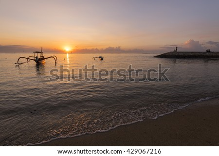A twin Jukung boat during a beautiful morning at Karang Beach, Sanur Bali Indonesia - stock photo