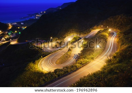 A twisty and curvy road to the top of the mountain. - stock photo