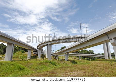 A twisty complicated elevated highway system through a grassy field against a blue cloudy sky. - stock photo