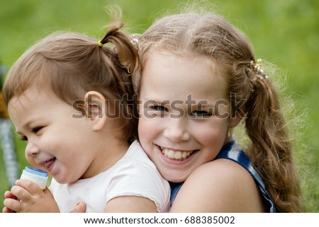 A two babies sisters playing in park, outdoor portrait