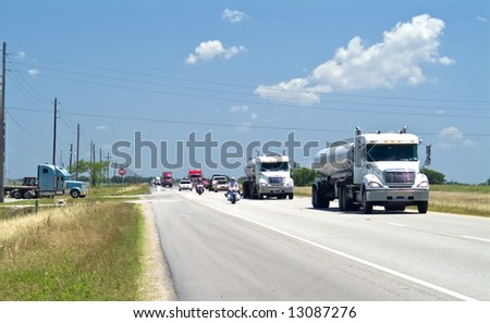 A two lane highway filled with eighteen wheelers and a few cars and motorcycles.