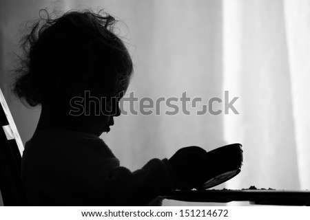 A two year old girl is sadly looking into her empty bowl wishing she had more to eat. / Hunger - stock photo
