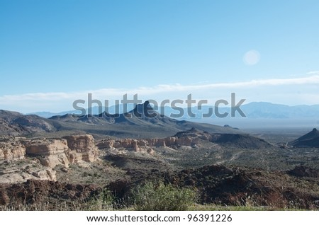A typical Arizona landscape with desert, weathered rocky buttes and distant mountain peaks. - stock photo