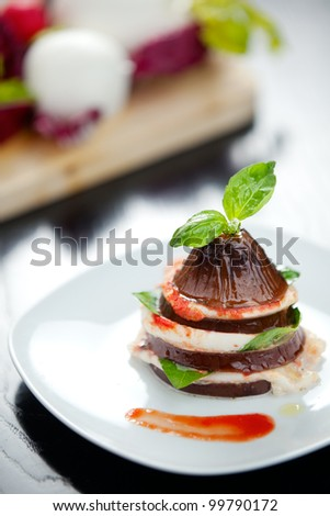a typical italian Provolone cheese and its use in a stuffed red bell pepper. Shallow depth of field on Bell pepper's stuffing - stock photo