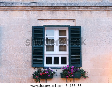 a typical maltese window with louvered shuters and square paned windows with flowers in hanging flower pots - stock photo