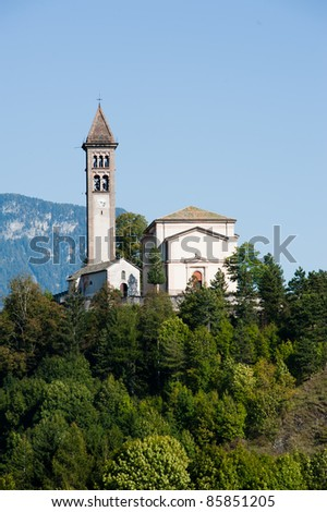A typical mountain church with a tall bell tower on top of a mountain surrounded by beautiful woods in Fiemme, Dolomites, Trentino, Italy.