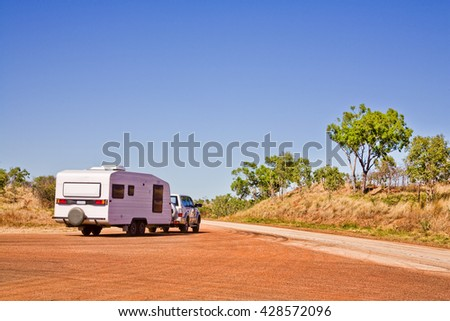 A typical outback touring rig heads back onto the road at a Western Australian rest area.