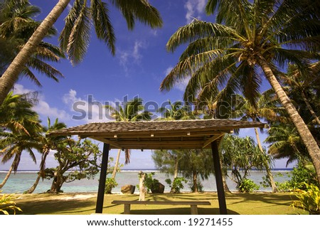 A typical roadside shot in the tropical Polynesian island of Rarotonga (Cook Islands) featuring lagoon, beach, palm trees and road shelter. - stock photo