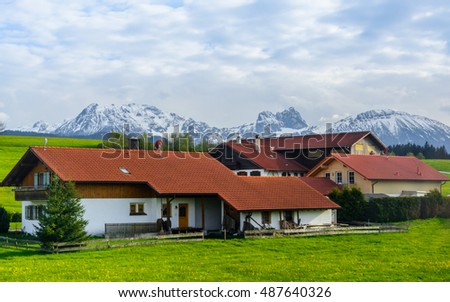 A typical traditional farmhouse on the Alpine meadow near St. Wolfgang city - the view from the spring green valley on the stone house on the background of shine sky with clouds and rocks, Austria