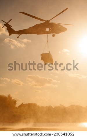 A UH-60 Blackhawk helicopter carries a humvee over a river at sunset. - stock photo