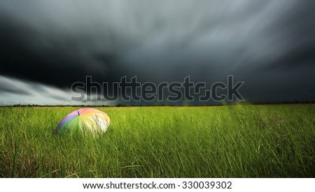 A umbrella on green field and dark blue stormy cloud. - stock photo