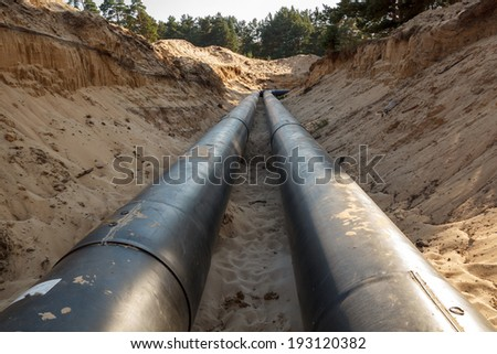 A uncovered pipeline construction site with sand around it - stock photo