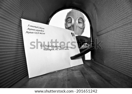 A unidentifiable person in a Gas Mask retrieves or sends mail from their mail box with an extension grabber so they do not touch the mail with their hands, for fear of disease or anthrax or more. - stock photo