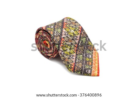 A unique, rolled-up necktie made of 100% Thai silk, hand-woven into intricate traditional patterns isolated on white background as a fashionable accessory