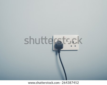 A United Kingdom standard wall socket on a blue wall with a cord plugged in to it - stock photo