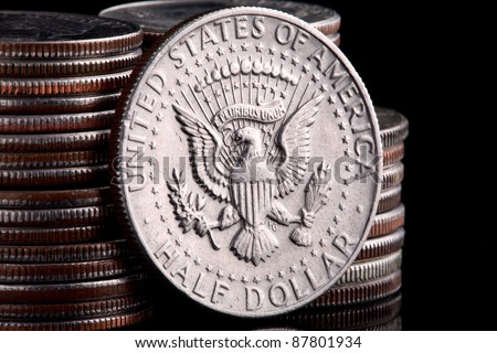 A US Kennedy Half dollar coin leaning against a stack of Washington Head Quarter Dollars - stock photo
