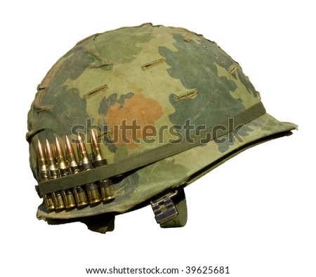 A US military helmet with an M1 Mitchell pattern camouflage cover from the Vietnam war, and six rounds of 7.62mm ammunition. - stock photo