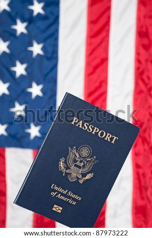 A USA passport with an American flag in the background - stock photo