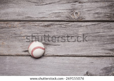 A used hardball sits on a rustic wooden background. Plenty of copy space surrounds the ball. - stock photo