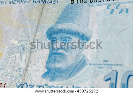 A used 100 Turkish Lira banknote showing the composer Buhurizade Mustafa Itri.  Banknote photographed at an angle. - stock photo